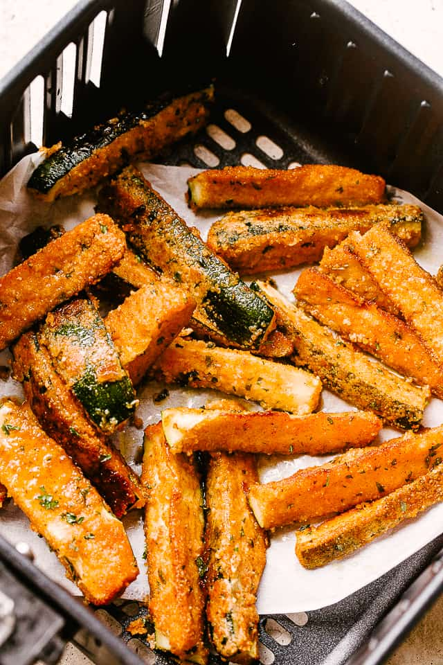 Air fryer basket with zucchini fries