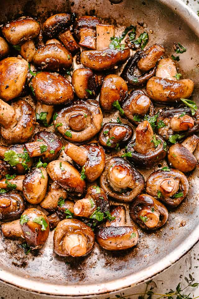 Skillet with cooked garlic butter mushrooms