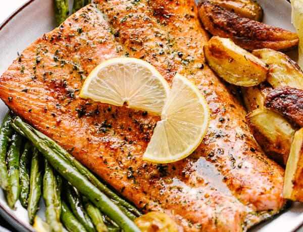 Broiled salmon plated with potatoes and greenbeans and garnished with lemon wedges
