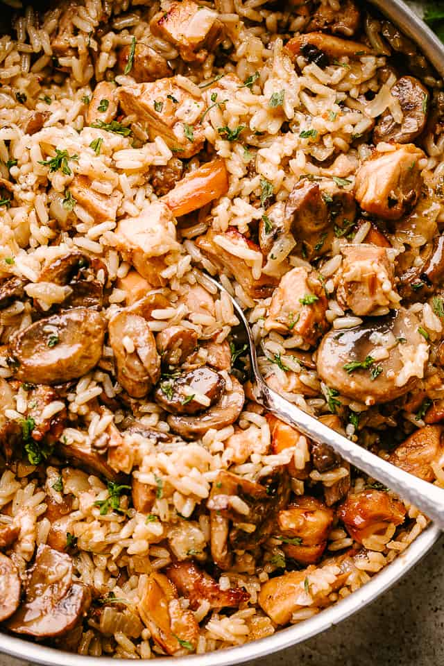 Chicken and mushrooms sauteing in a pan with rice