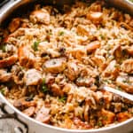 Chicken, mushrooms, and rice in a pan being stirred
