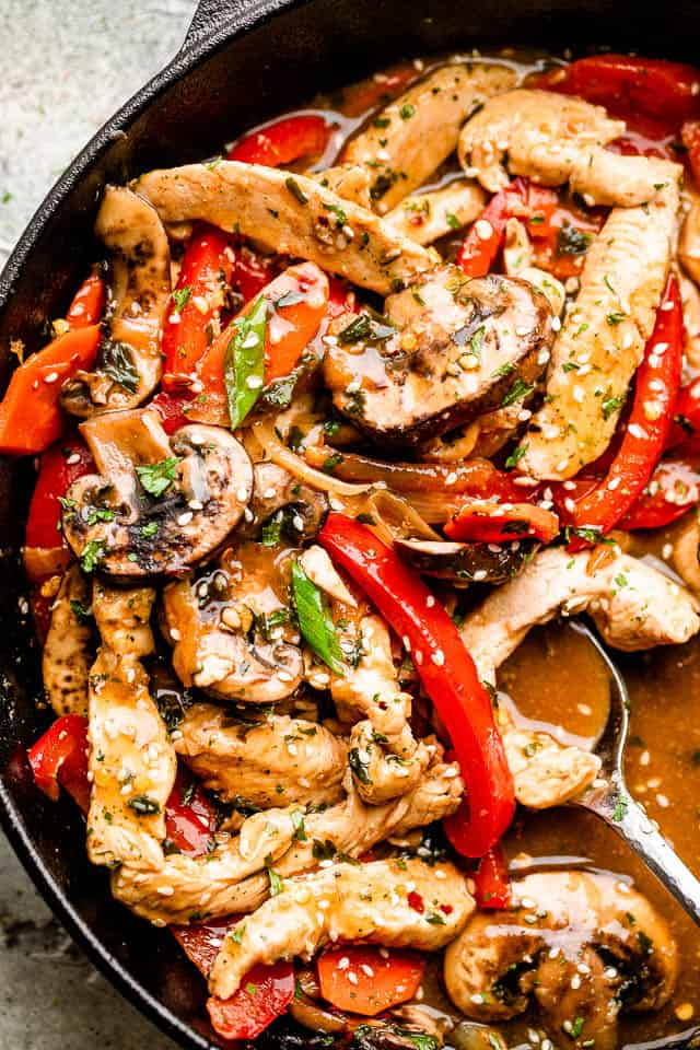 Chicken stir fry. topped with sesame seeds and green onion in a pan, ready to be served.