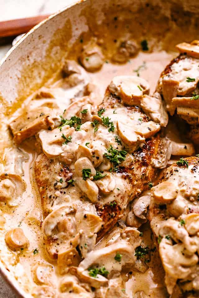 Creamy mushroom chicken in a skillet garnished with fresh herbs