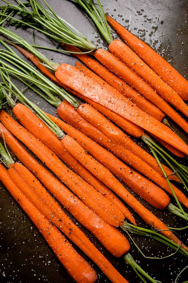 Raw carrots dusted with salt and pepper ready for roasting.