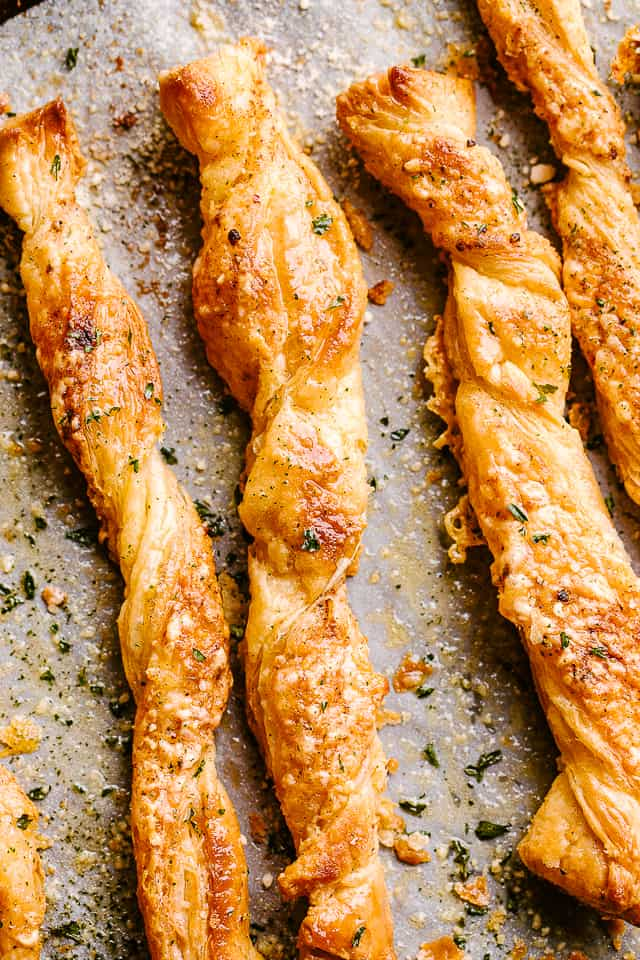 Puff pastry cheese sticks fresh out of the oven on their baking sheet.