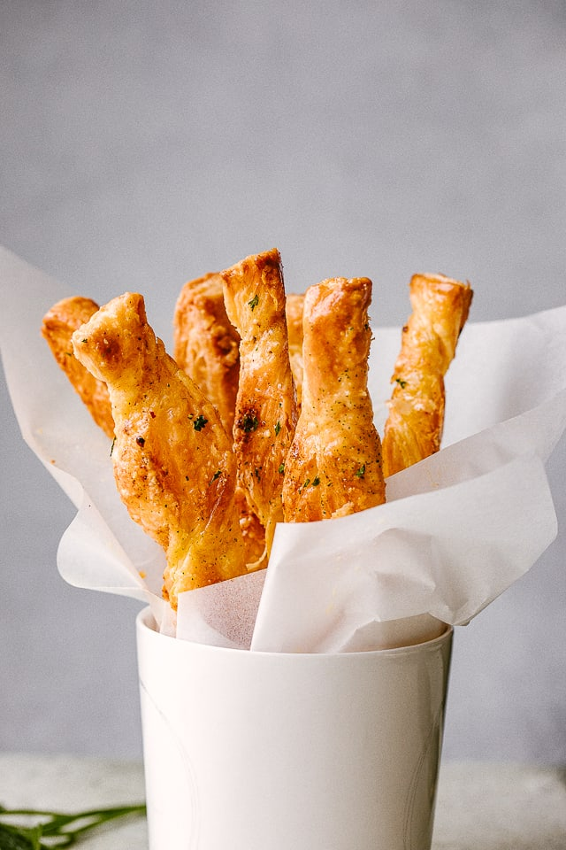 Puff Pastry sticks ready to serve in a white cup.