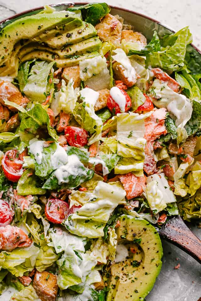Salmon BLT Salad plated and tossed in creamy dressing
