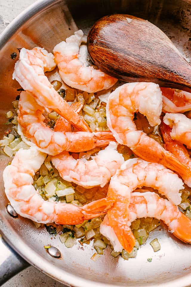 Shrimp sauteing in a pan with garlic.