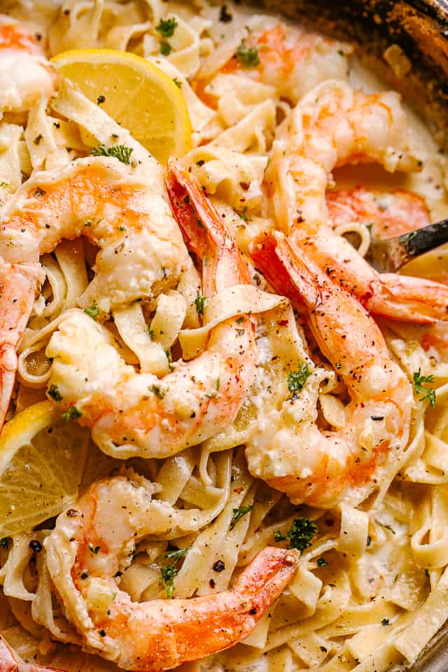Close up of Creamy Shrimp Alfredo Pasta in a pan garnished with lemon wedges.
