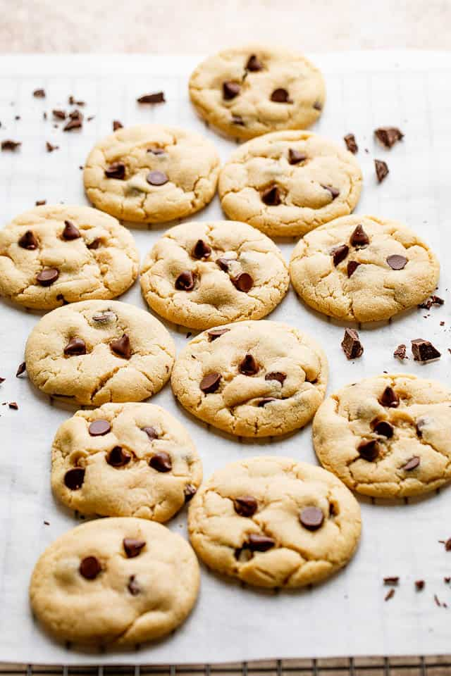 Perfectly cooked chewy chocolate chip cookies cooling on a parchment lined rack.