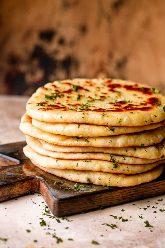 Stack of homemade flatbread on a wooden board.