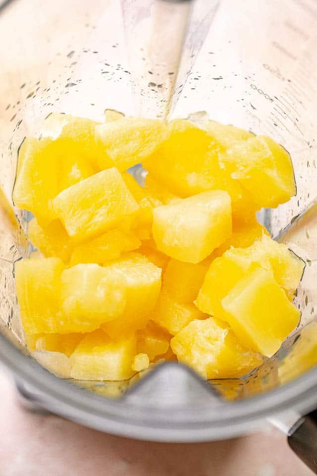 Frozen pineapple in the blender ready to be blended.