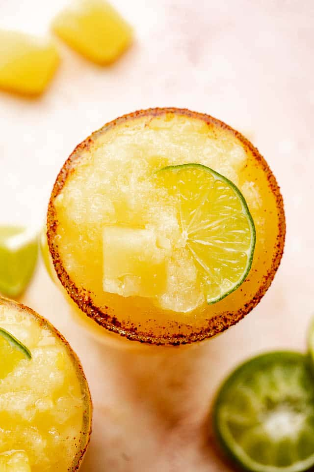 A top view of glass with frozen pineapple margaritas and a chili salt rim.