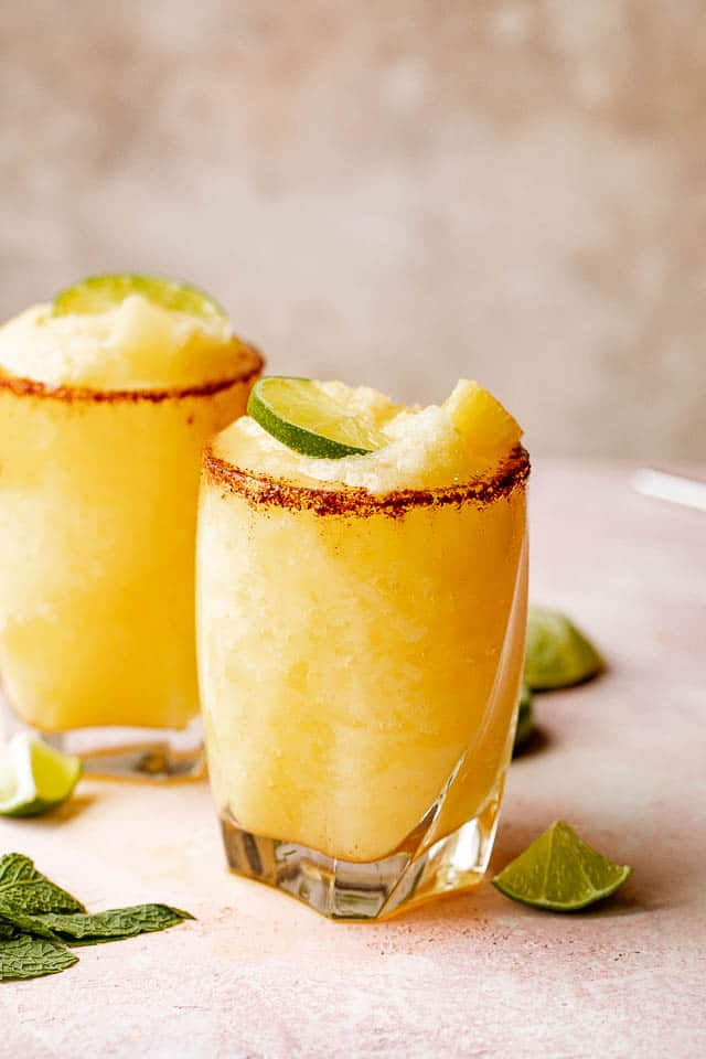 Two glasses of frozen pineapple margaritas with a chili salt rim garnished with lime and mint.