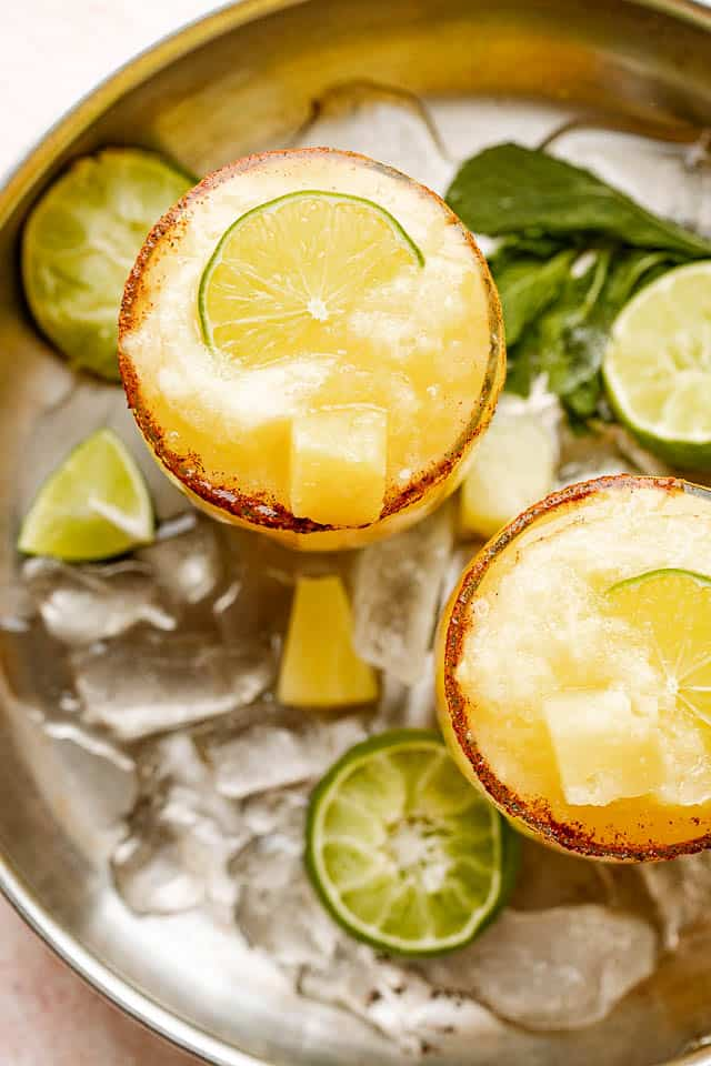 top view of frozen margaritas garnished with limes and pineapples
