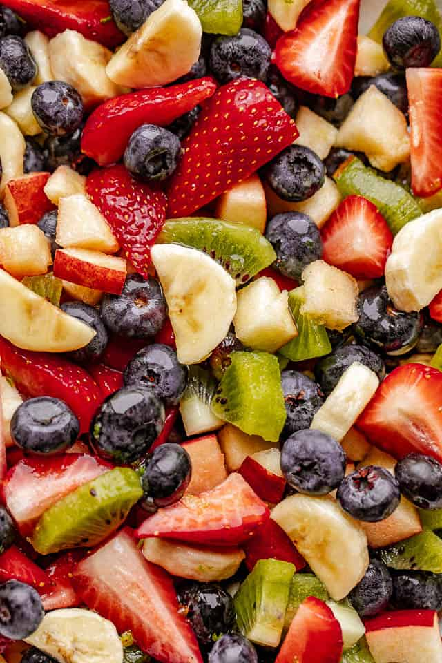 Close up of strawberries, blueberries, kiwis and bananas tossed with honey lime dressing.