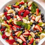 Fresh fruit salad in a large white bowl garnished with fresh mint leaves.