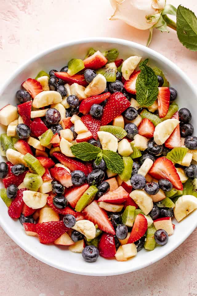 Mixed fresh fruit in a large white bowl garnished with mint leaves.