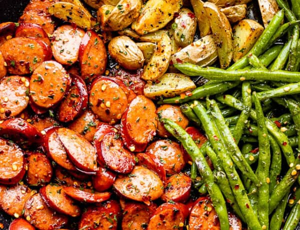 close up of potatoes, green beans, and sausage slices in a black skillet
