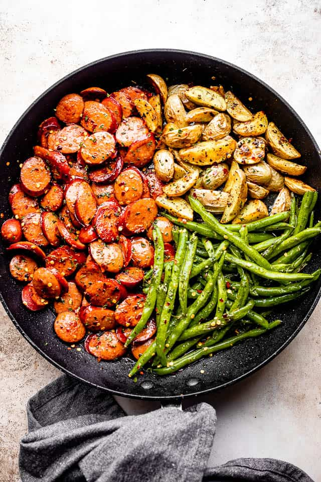 grey linen kitchen towel next to a black skillet filled with andouille sausage slices, potatoes, and green beans