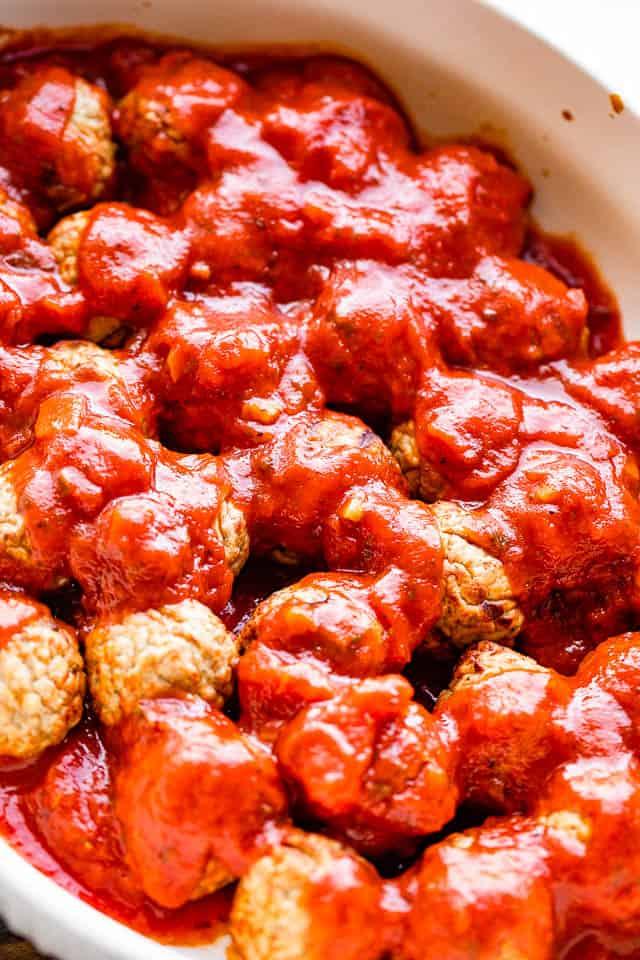 pouring marinara sauce over meatballs