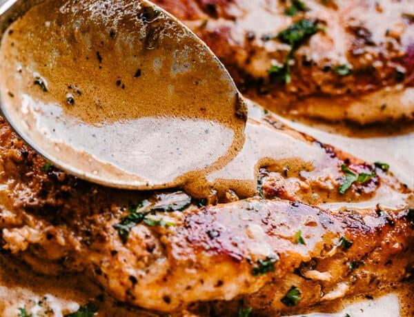 spooning creamy balsamic sauce over chicken