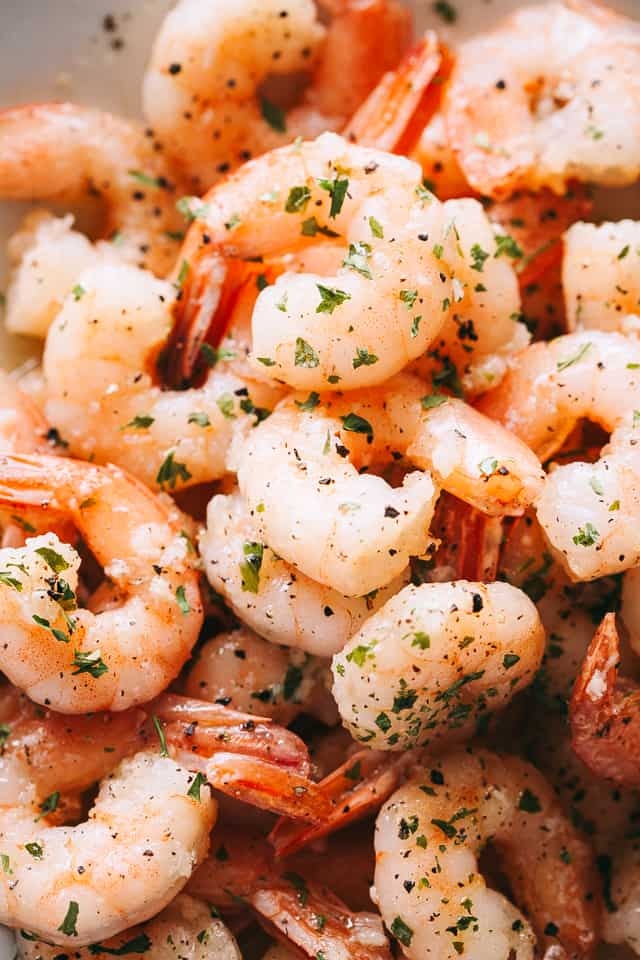 up close photo of cooked shrimp in a white skillet