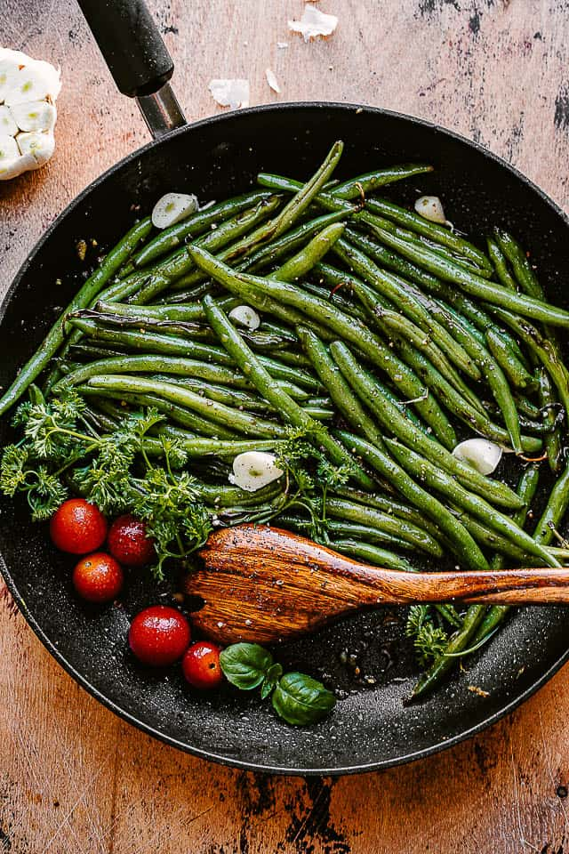 green beans, tomatoes, and garlic cloves in a black skillet with a wooden spoon inside