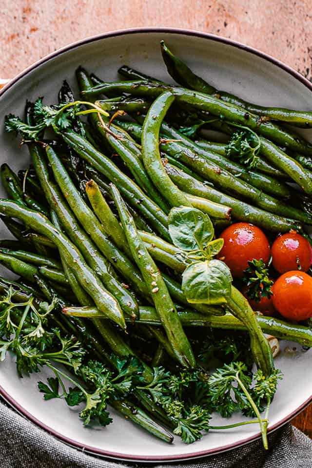 cooked green beans served in a bowl with fresh basil and cherry tomatoes