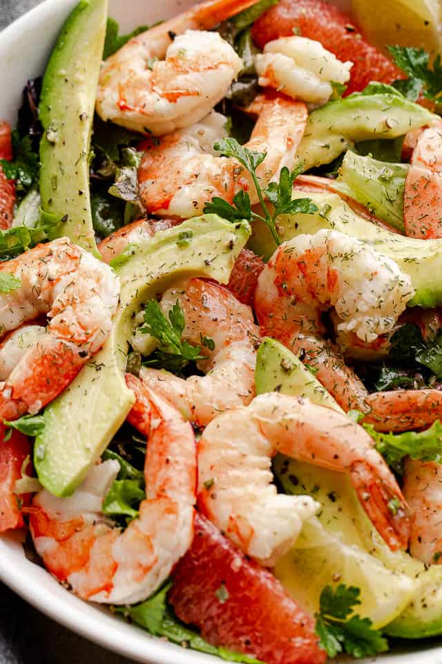 cooked shrimp, avocado slices, and salad greens tossed together in a white serving bowl