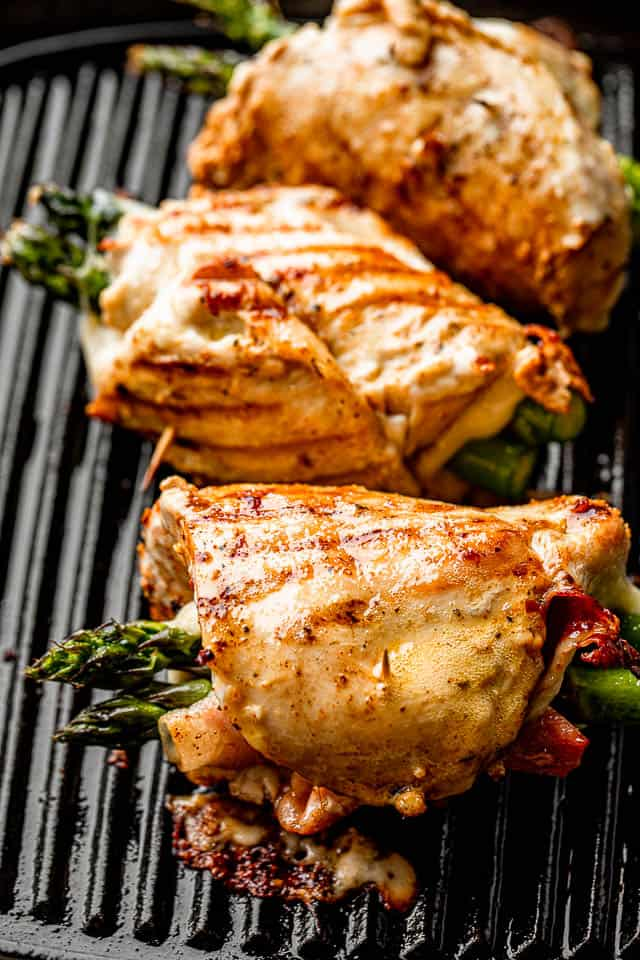 three chicken roll ups stuffed with asparagus, prosciutto, and cheese, and cooking on a grill pan