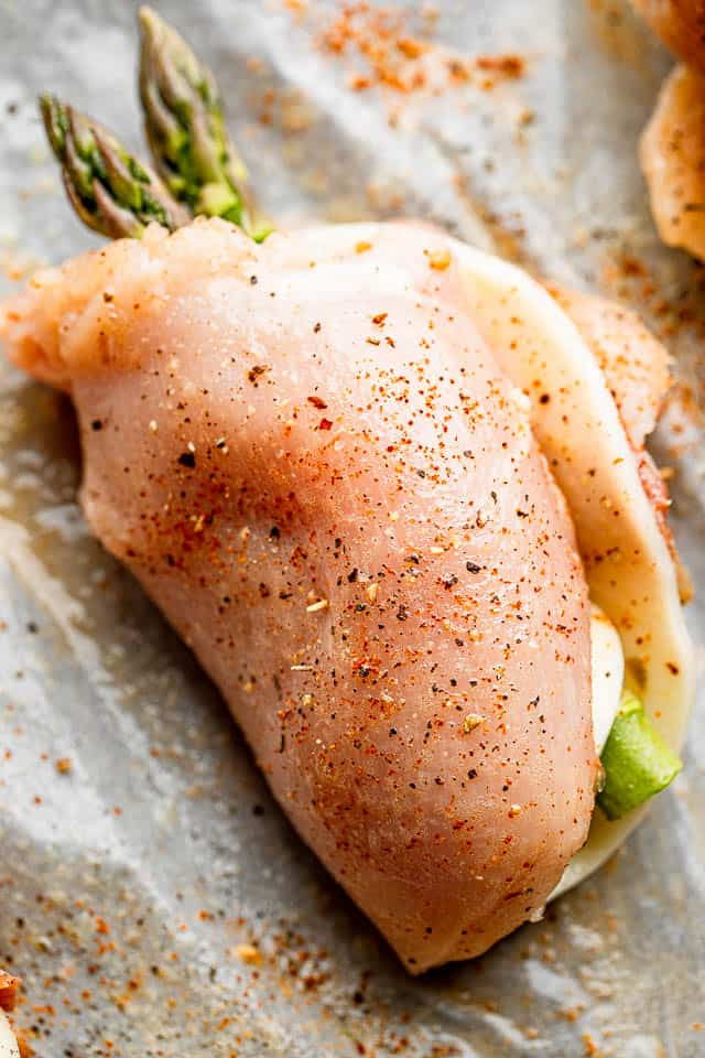 raw chicken breast rolled up with asparagus spears and cheese slice