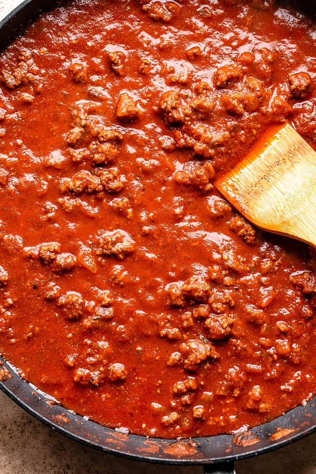 making tomato sauce with beef in a black skillet