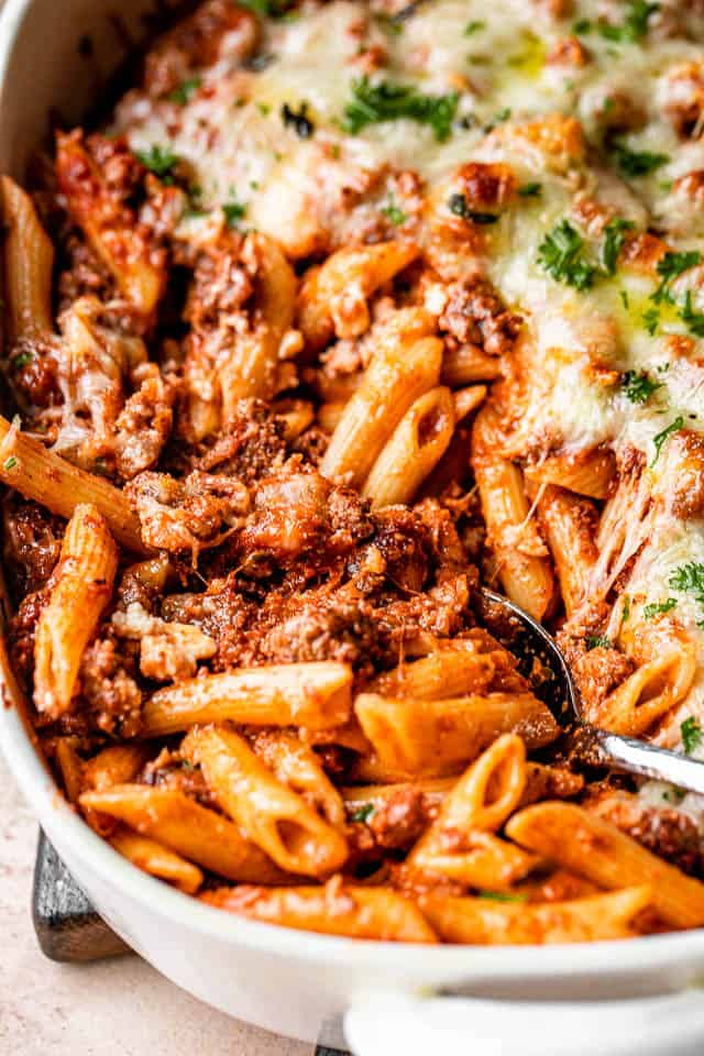 scooping out baked ziti pasta from a baking dish
