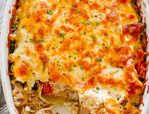top view of chicken fajita casserole in an oval baking dish topped with melted cheese