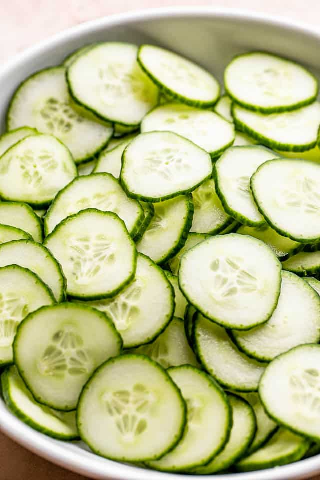 sliced cucumbers in a white bowl prepped for a salad