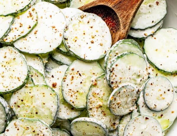 salad bowl filled with sour cream covered cucumbers sprinkled with cracked black pepper
