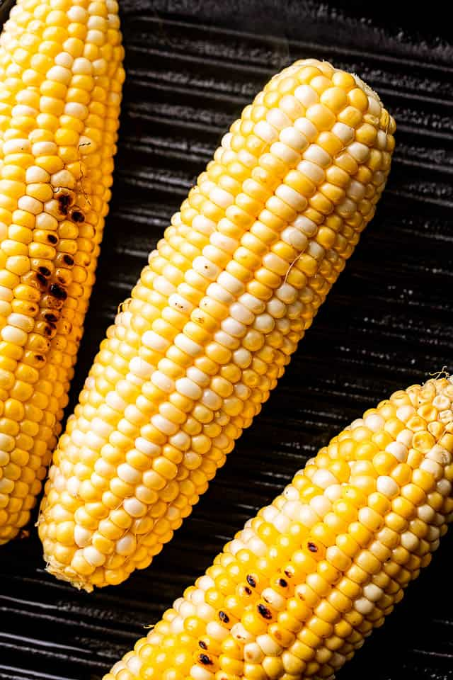 3 ear cobs of corn on the grill