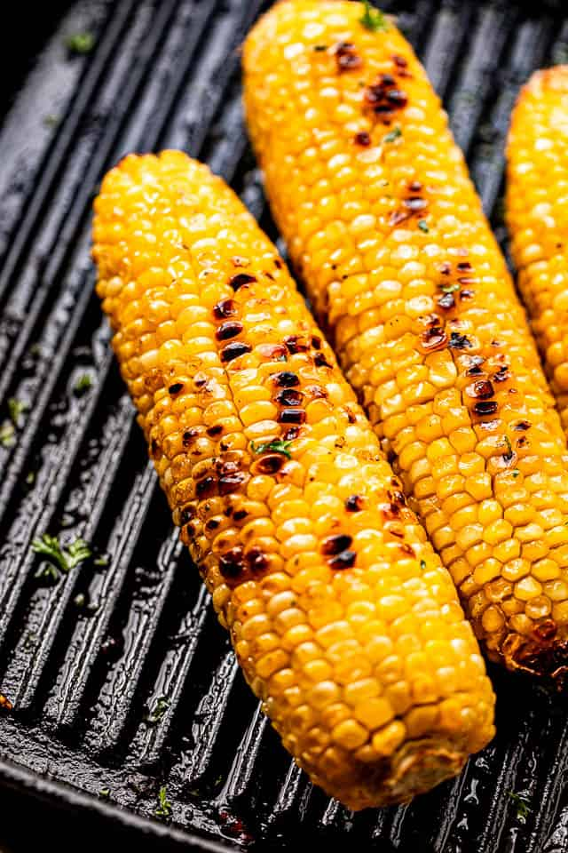 charred cobs of corn on a grill