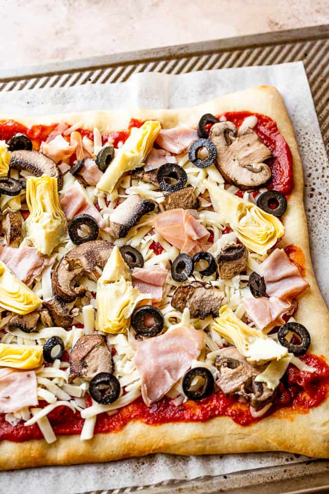 tomato sauce, cheese, artichoke hearts, olives, and ham on top of pizza crust prepared for grilling