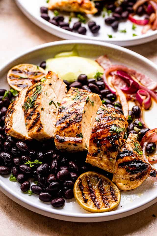 Grilled Mojo Chicken Breast cut in slices and served over black beans and guacamole to the side.