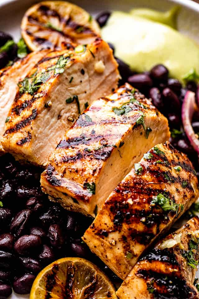 Sliced grilled chicken breast set over black beans