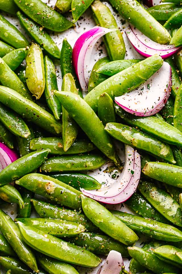 close up of raw snap peas and onions tossed with seasonings