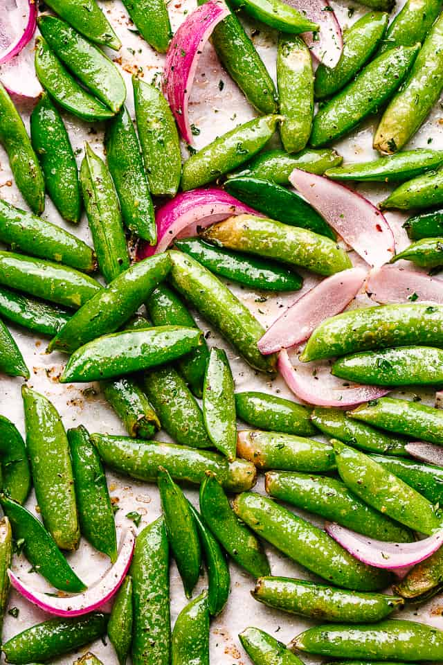 top view of roasted sugar snap peas and sliced red onions
