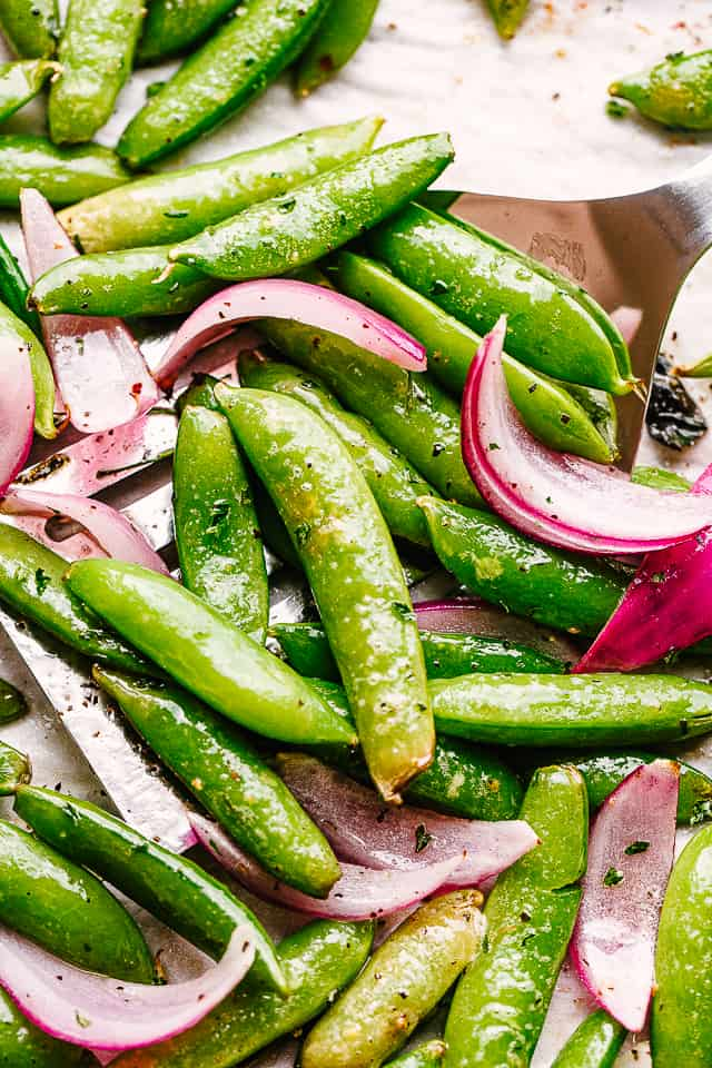 scooping up roasted snap peas from a baking sheet