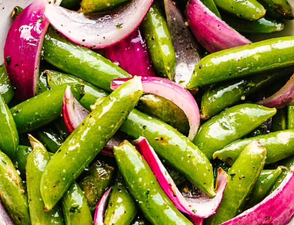 roasted sugar snap peas with red onions served in a cream bowl