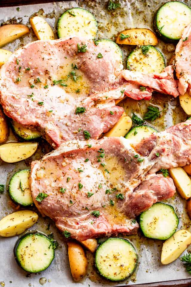 baking sheet with raw pork chops set on top of squash slices