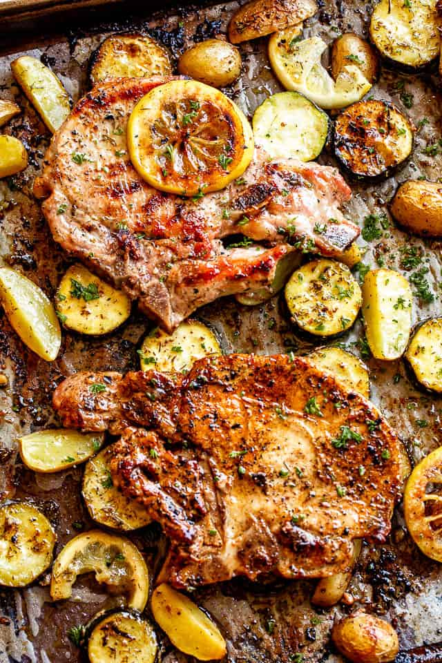 sheet pan with baked pork chops on top of slices of squash and lemons