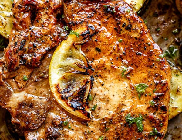close up top view shot of baked pork chops topped with a slice of lemon