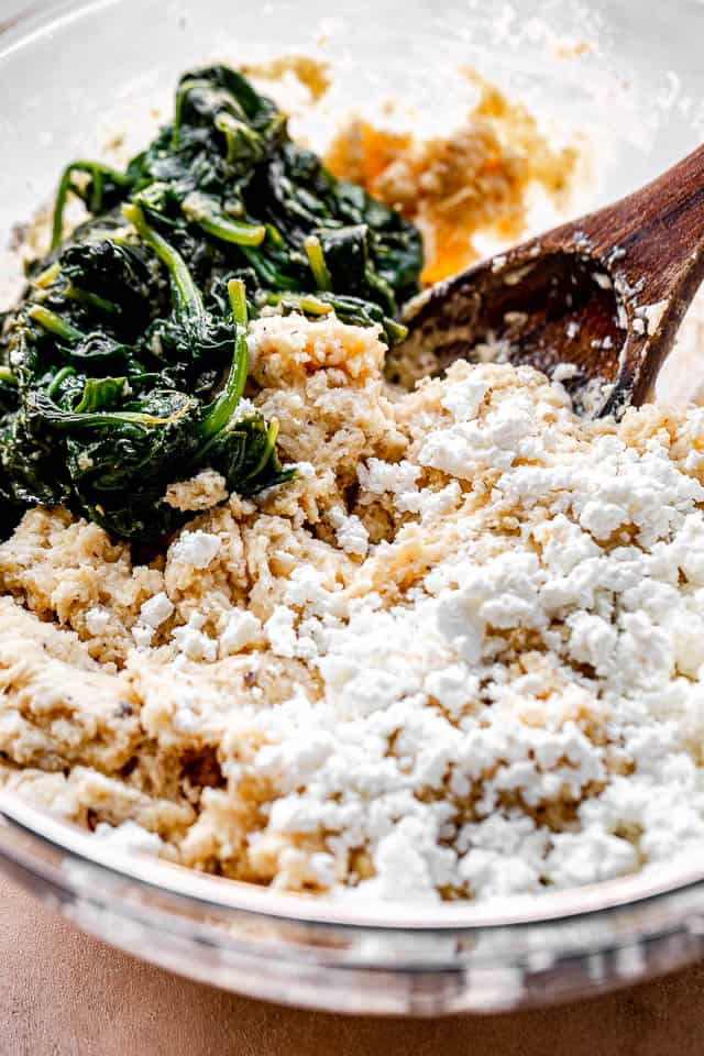 side view of a mixing bowl with spinach, cheese, and flour